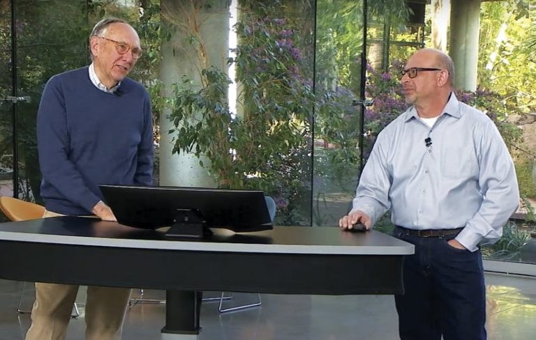 Jack Dangermond and Jim McKinney standing at a desk with a computer monitor on it