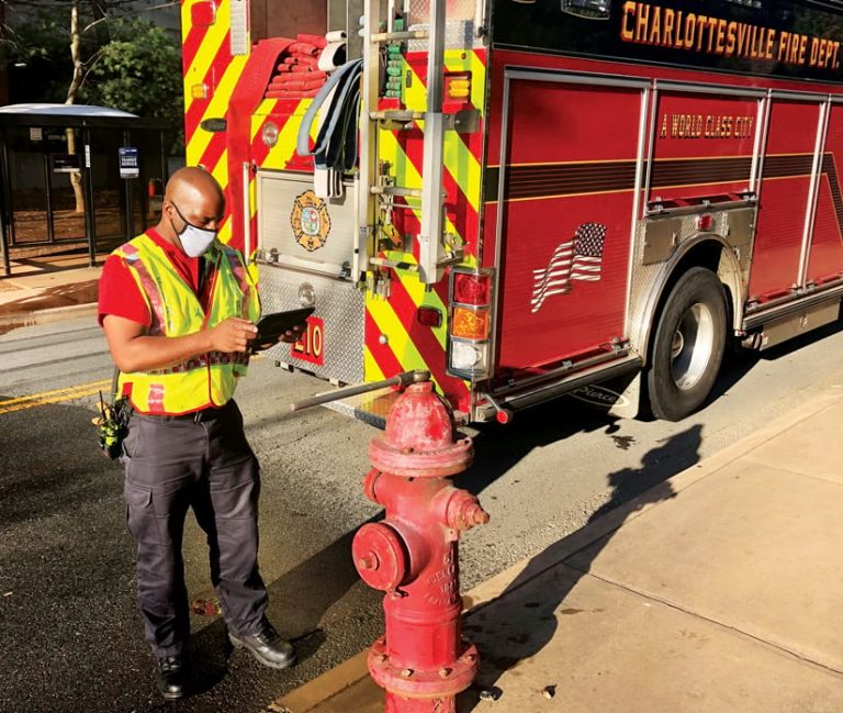 A firefighter standing next to a fire hydrant using a tablet to record an inspection
