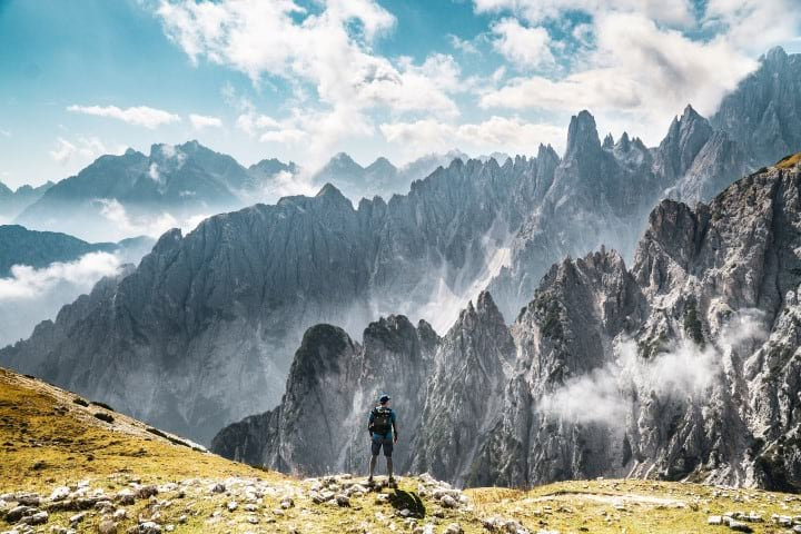 A hiker overlooks a rocky alpine vista in Italy.