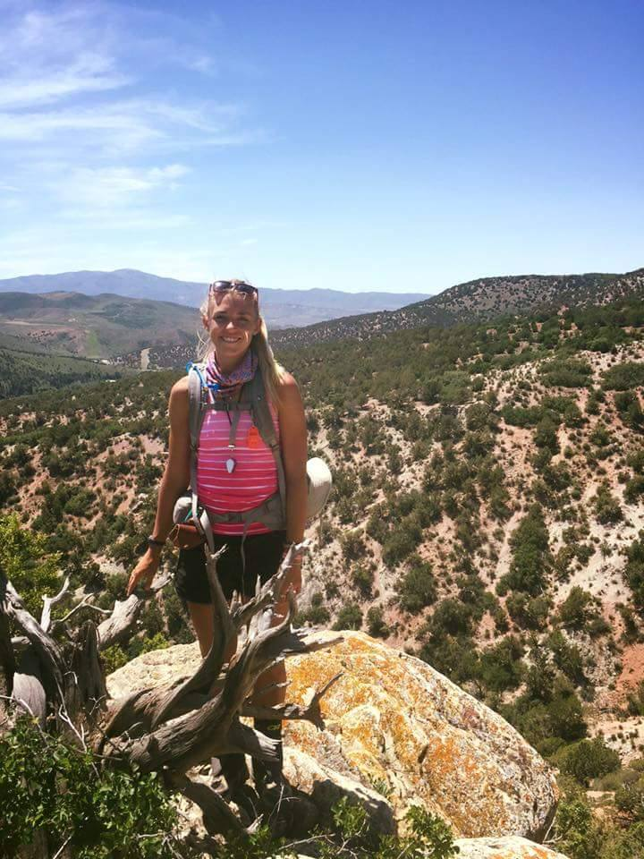 Amanda Huber poses for an outdoor picture as she hikes in the mountains.