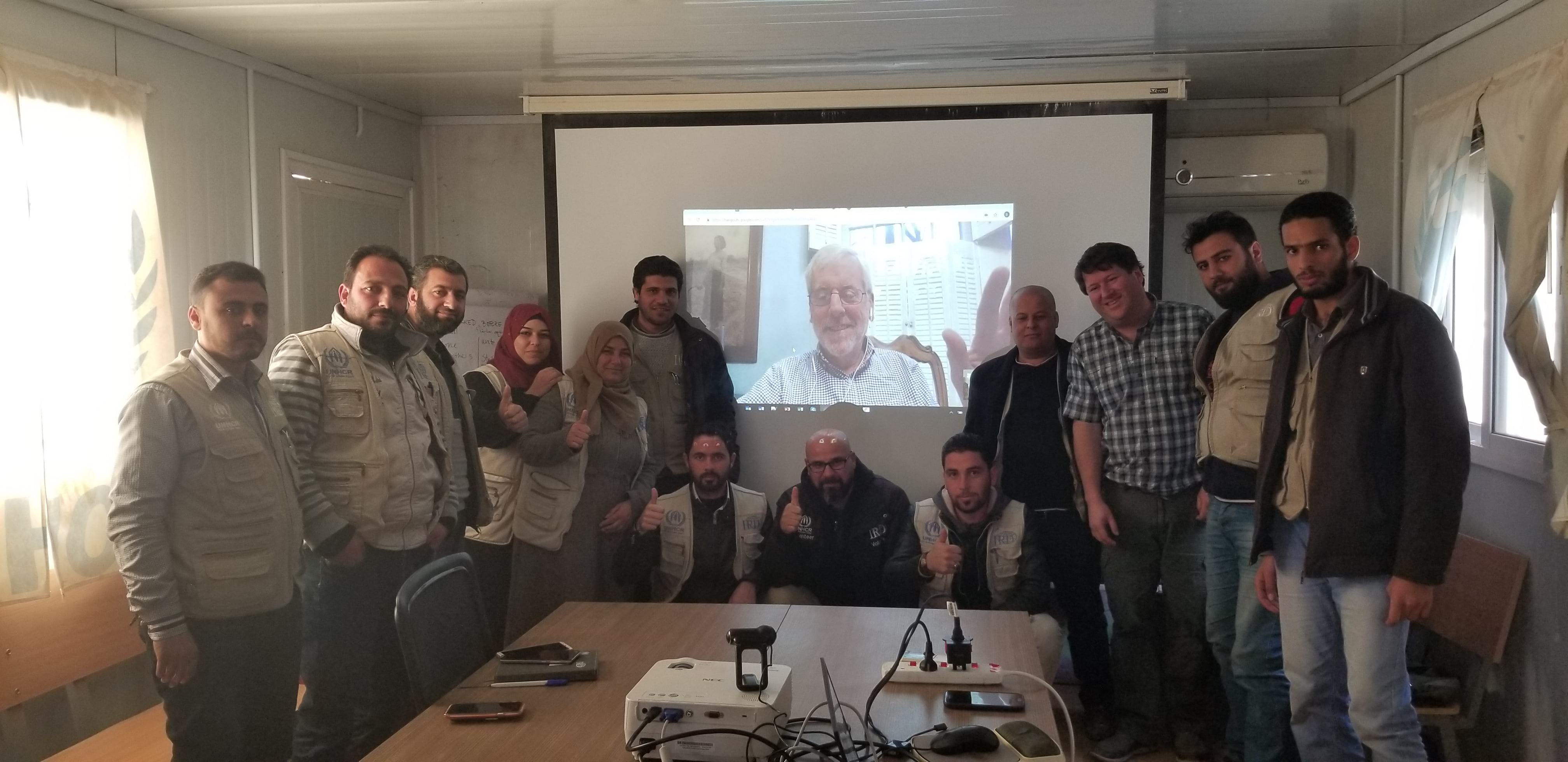 RefuGIS paticipants pose for a photo next to Allen Carroll's video stream