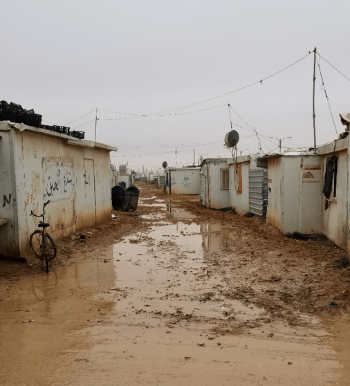 A muddy, shelter-lined road in the refugee camp