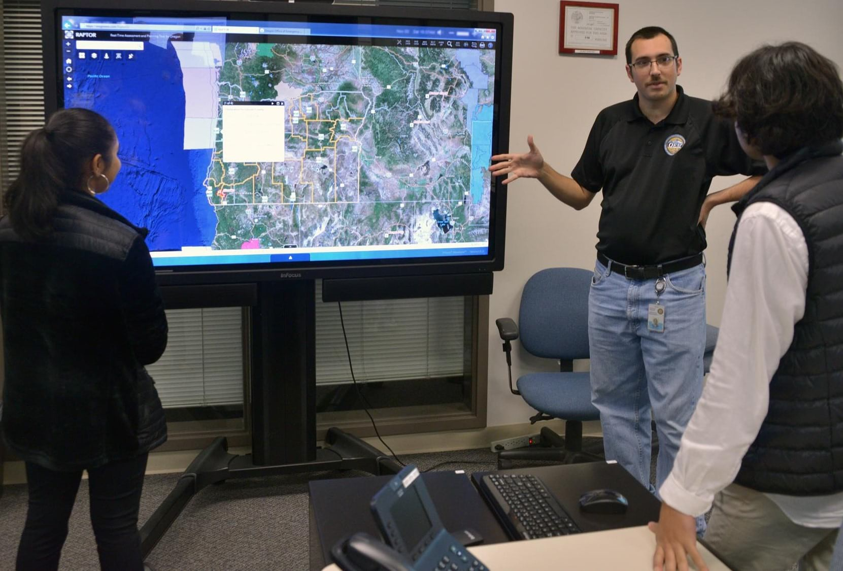 Daniel Stoelb, GIS program manager for Oregon's Office of Emergency Management, discusses the RAPTOR application with two students