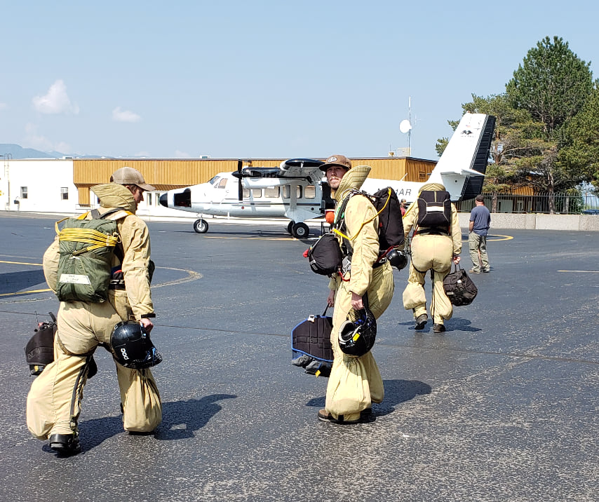 Two smokejumpers prepare to load a plane