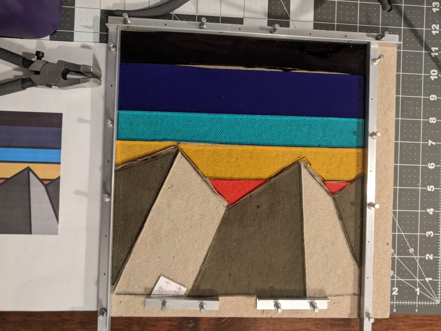 "Stained glass is laid out on a table to form a multicolored mountain design. The work-in-progress craft inspiration for the vibrant ""stained glass"" look of the 3D storm tracks. (Design credit: Silvia Casas)"
