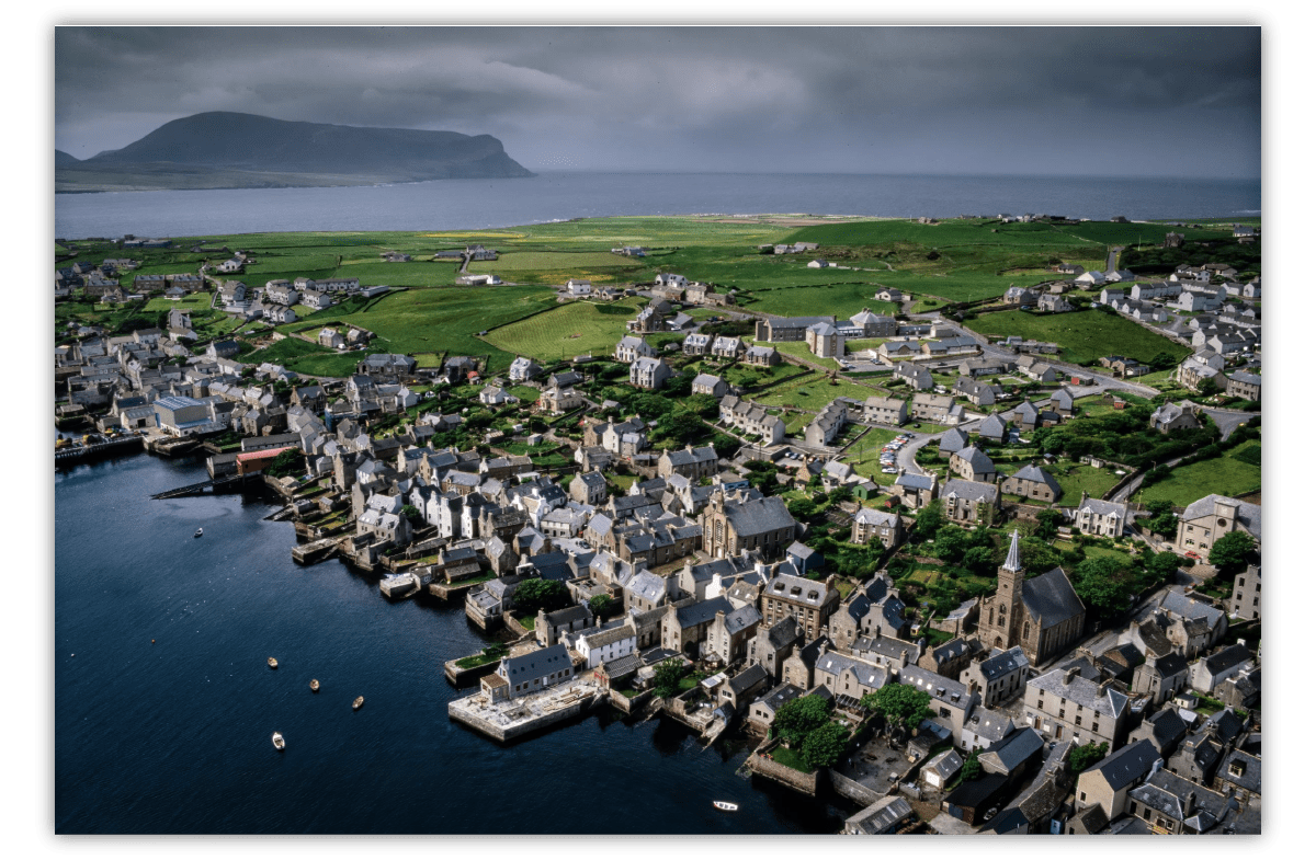 An aerial shot of a historic fishing village showing clustered stone buildings on the waterfront, with expansive green fields behind them