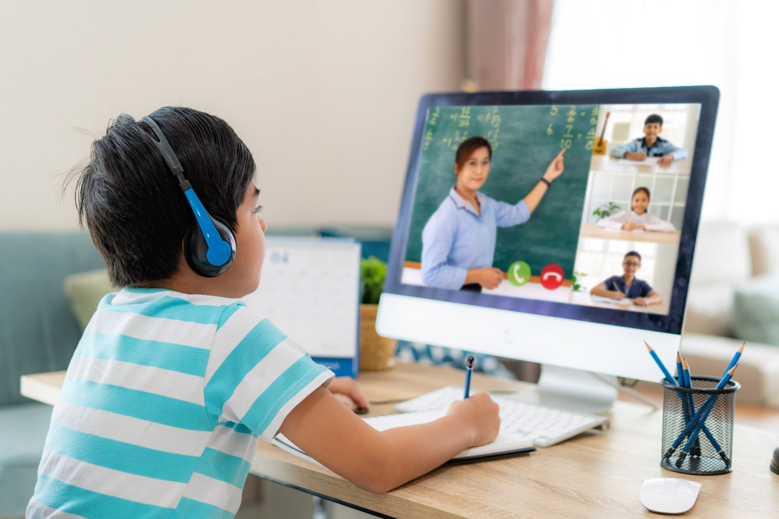Elementary aged student attending school from home using a computer