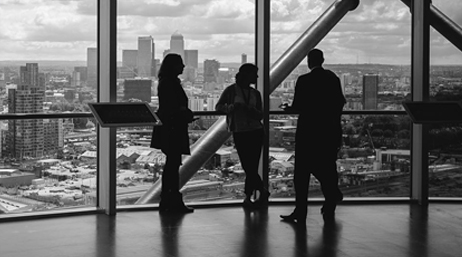 Three people stand in an observation room overlooking a city