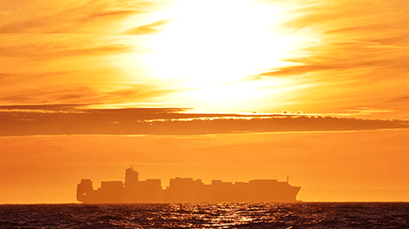 Large shipping vessel carrying shipping containers traveling on the water at sunset