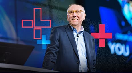 Esri president Jack Dangermond smiling on stage at a conference