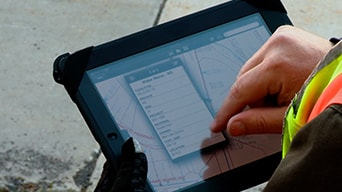 Person using tablet loaded up with GIS software showing real-time data
