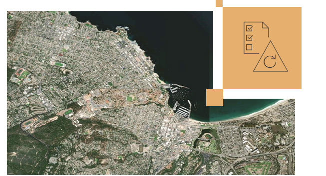 Satellite map of a city with green land and buildings in gray and a small image of a paper with check marks