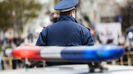 Male police officer with blue hat and jacket standing by a blue and red police car siren