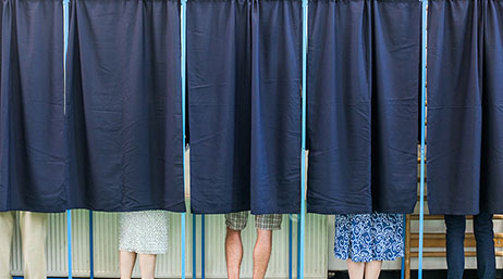 Several people standing behind a blue curtain representing a voting poll station