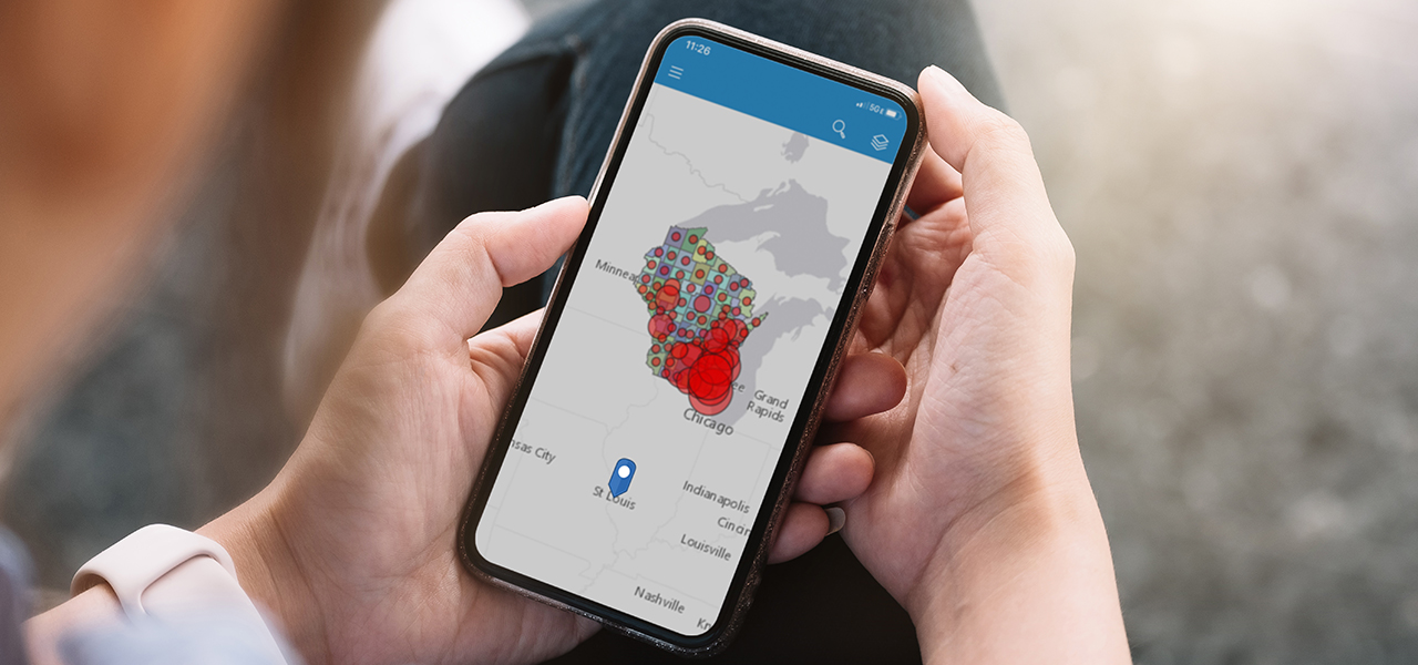 Two hands holding a cell phone that shows a map of Midwestern states