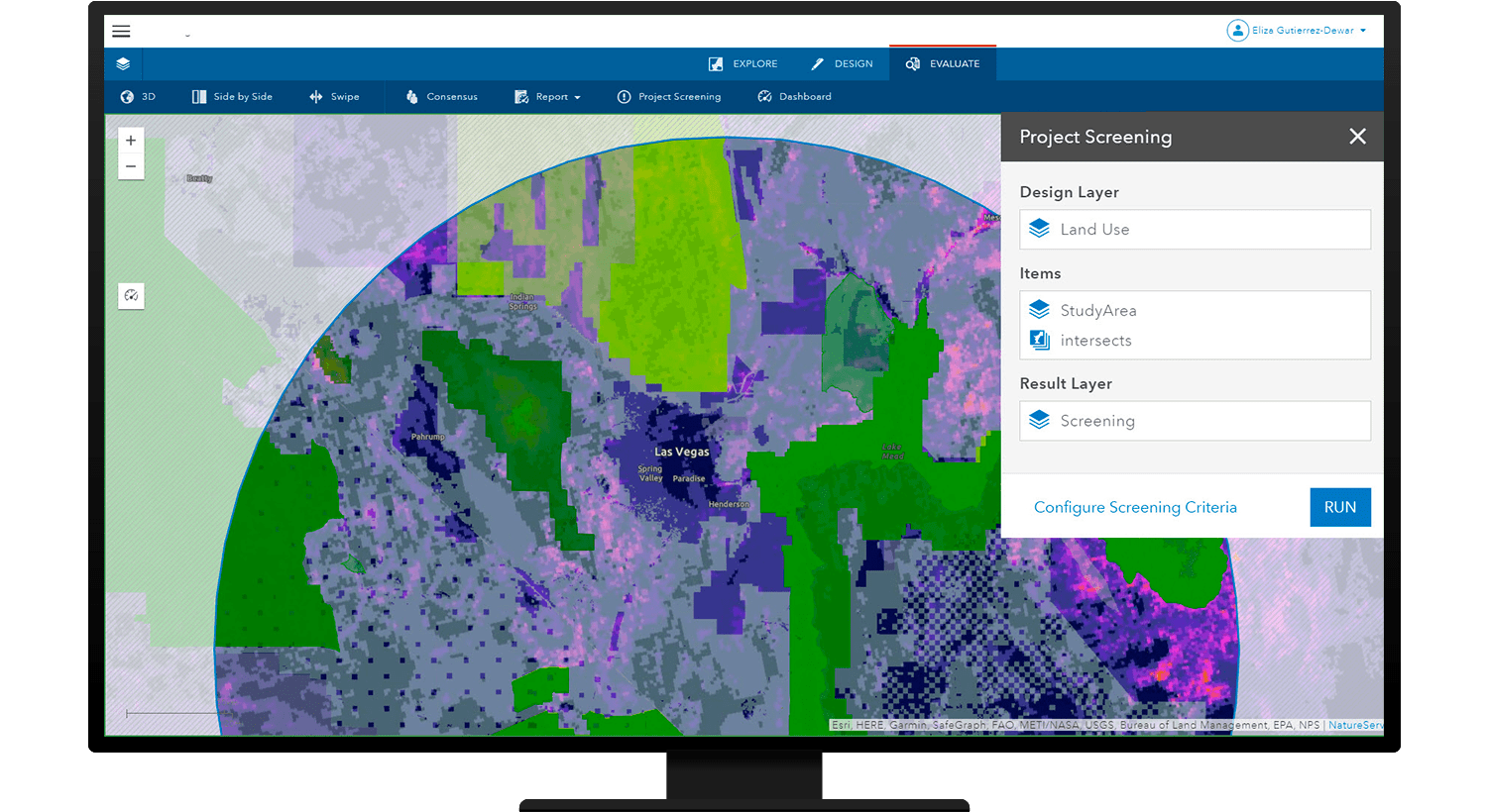 Monitor displaying a multicolored digital map with a popup box showing the project screening option in ArcGIS GeoPlanner