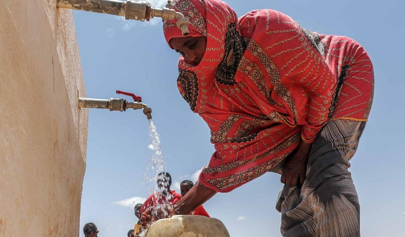A woman fills a water bucket at  a community fountain