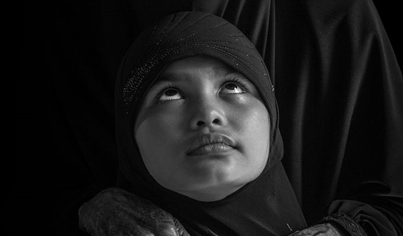A close-up of a child dressed in black looking up at another person