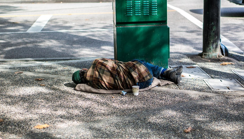 A person sleeps outside on a sidewalk next to a green traffic light