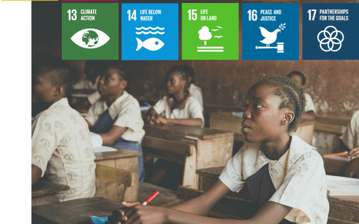 A photo of students at desks in a classroom with five Sustainable Development Goals icons displayed across the top