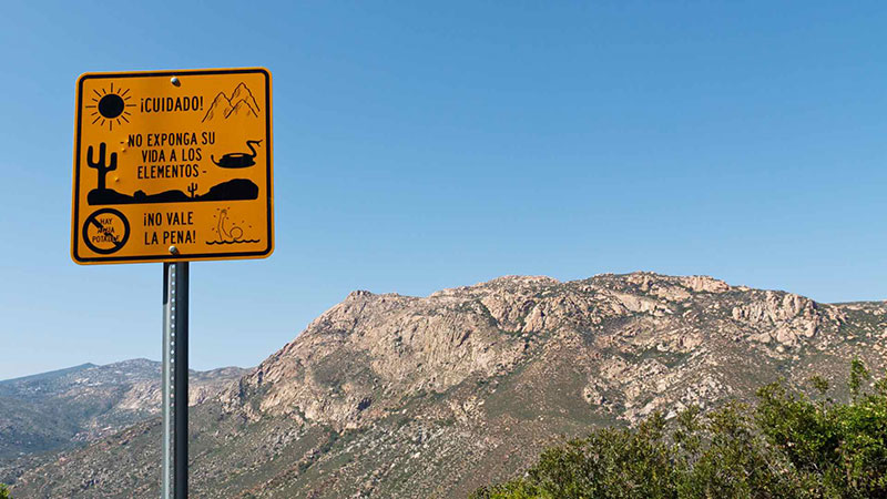 A yellow border crossing sign appears before mountains in the Southwestern United States
