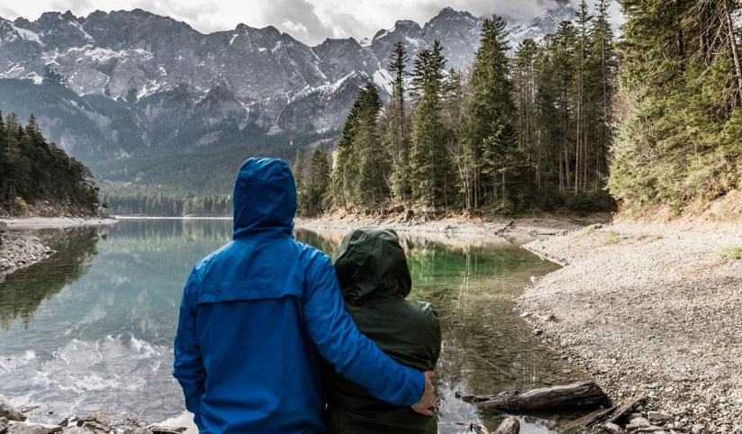 A couple standing closely together while looking at the view of a forested lake with snowy mountains in the distance