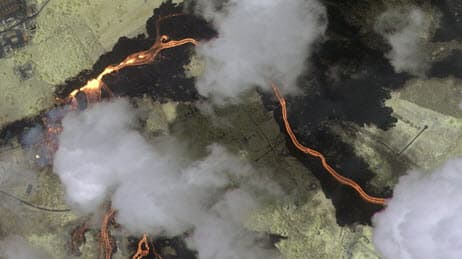 Aerial view of a lava flow with clouds above it
