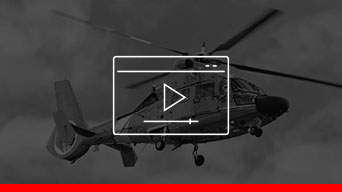 A black and white image of a helicopter in flight, overlayed with a white outlined video player icon