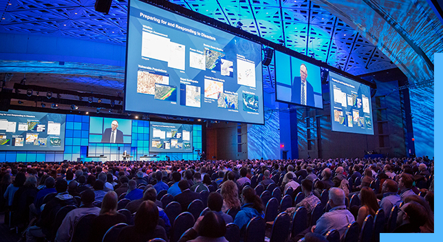 A large conference stage with speaker, big screens, and an audience.