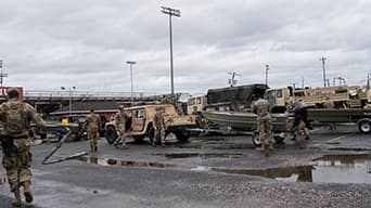 Photograph of military personnel in a lot with various military vehicles