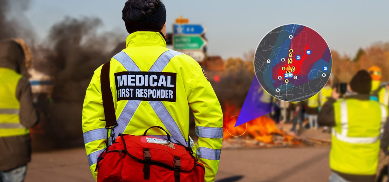 A medical first responder with medical supplies standing near a fire
