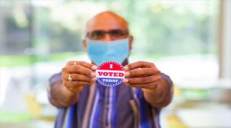 "Man wearing a face mask and holding an ""I voted today"" button."