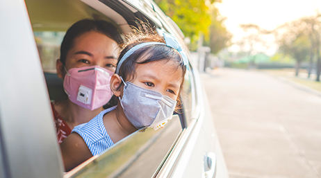Woman and child wearing face masks in a car