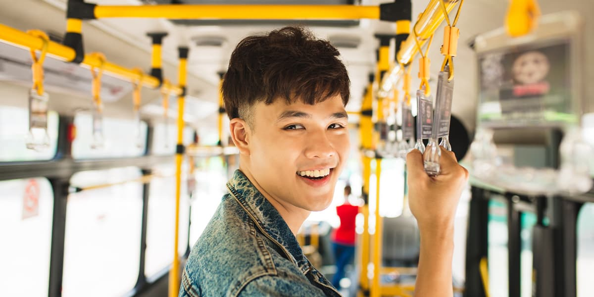 A happy young adult taking public transportation, standing on a bus