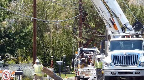 Two utility workers outdoors next to utility trucks performing maintenance on electrical poles