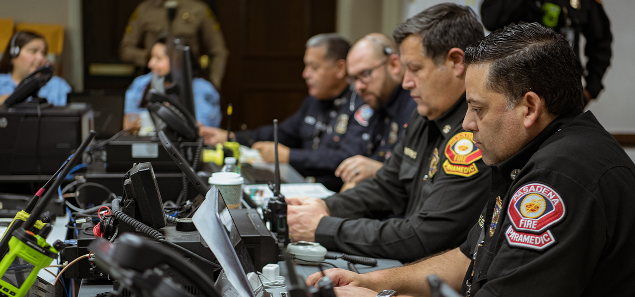 Pasadena Fire staff sitting at tables with phones, walkie talkies, and computers