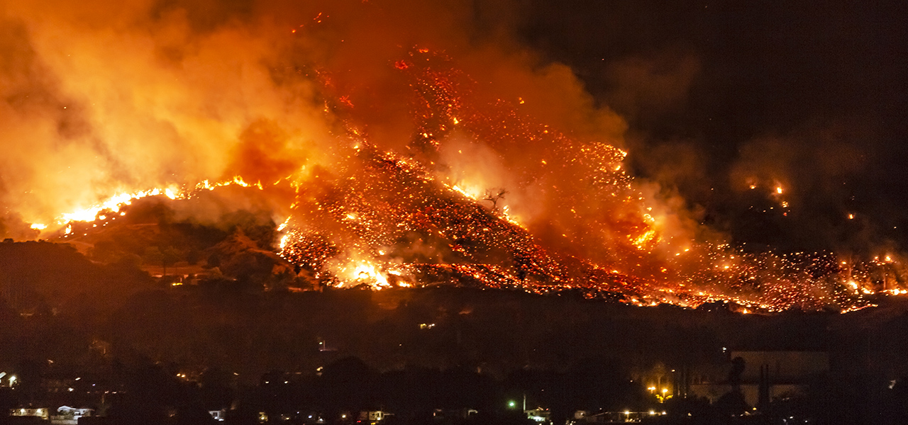 Fire burning across hills at night