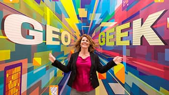 Conference attendee standing in front of Geo Geek sign