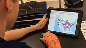 Image of a boy using a tablet with one arm in an orange cast