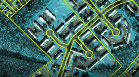 An aerial view of paths outlined in yellow that lead to multiple long, rectangular buildings