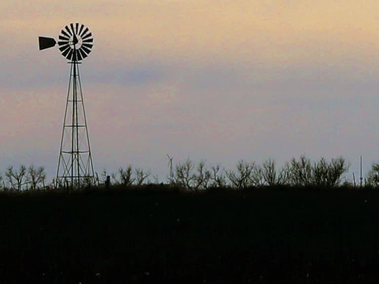 Photo of a windmill at sunset in an open field