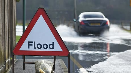 A triangular flood sign on the side of a road
