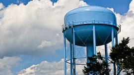 Image of a large blue water tower against a cloudy blue sky