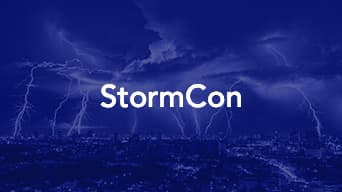 Blue over toned photo of a lighting storm overtop a city with the word 'StormCon' at the center