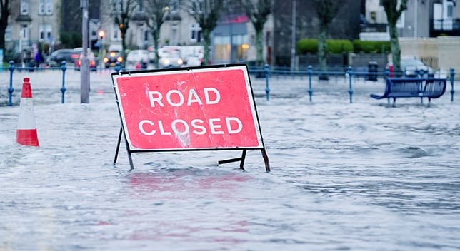 "A sign reading ""Road Closed"" stands in the middle of a flooded street"