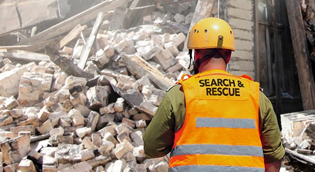 "A man wearing a hard hat and a reflective vest that says ""Search and Rescue"" stands near the remains of a collapsed building."