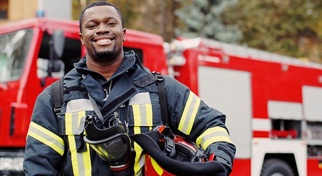 A firefighter in uniform stands and smiles in front of a fire truck