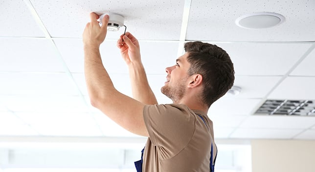 A technician installs a smoke detector on the ceiling