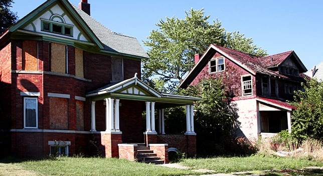Two two-story houses in disrepair sit on neighboring lots, one with boarded windows and the other with a poorly maintained roof