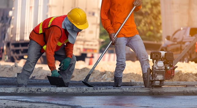 Two construction workers wearing bright orange shirts use handheld tools to level new pavement